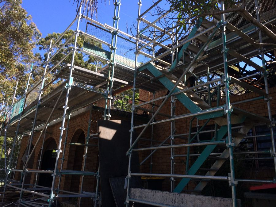 House demolition with safe asbestos removal shown with scaffolding